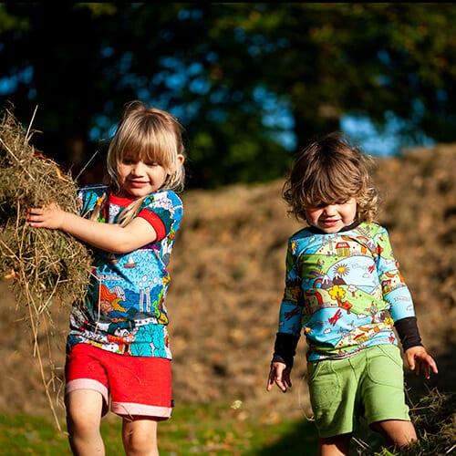 children wearing bright fun handmade clothing p;laying with hay